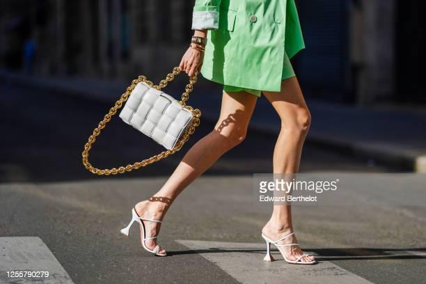 Leonie Hanne wears a pale green oversized long blazer jacket from Bernadette, pale green short pants from Bernadette, a Bottega Veneta white...