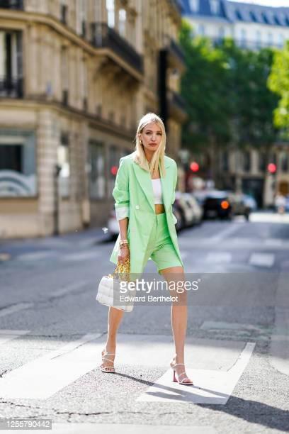 Leonie Hanne wears a pale green oversized long blazer jacket from Bernadette, pale green short pants from Bernadette, a white cropped top from Skin,...