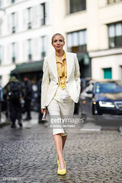 Leonie Hanne wears a pale orange shirt, a yellow mini bag from Jacquemus, a white mini bag from Jacquemus, a white blazer jacket, cropped pants,...