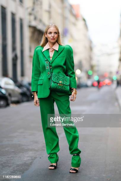 Leonie Hanne wears a pink shirt with a large collar a green blazer jacket with shoulder pads a green leather Givenchy bag with printed snake pattern...