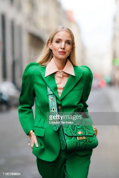 Leonie Hanne wears a pink shirt with a large collar, a green blazer jacket with shoulder pads, a green leather Givenchy bag with printed snake...