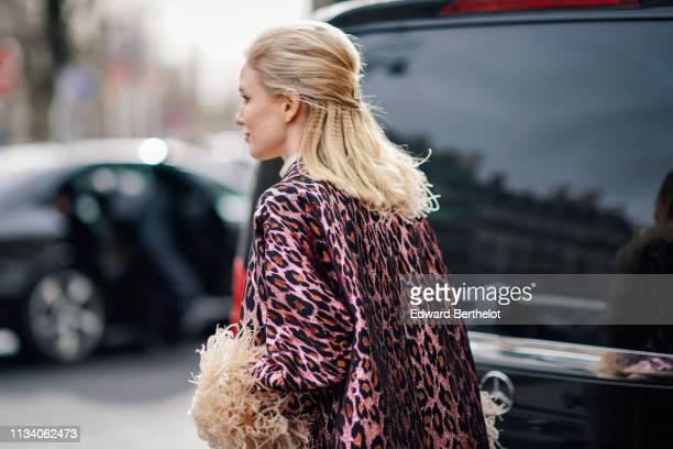 Leonie Hanne wears a purple leopard print jacket outside Miu Miu during Paris Fashion Week Womenswear Fall/Winter 2019/2020 on March 05 2019 in Paris...