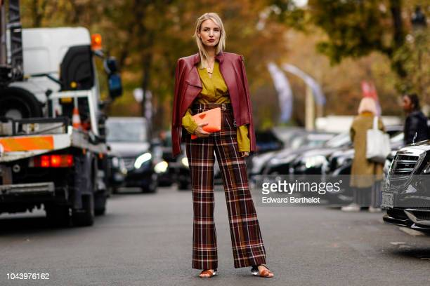 Leonie Hanne wears a red burgundy leather jacket a yellow top checked pants outside Akris during Paris Fashion Week Womenswear Spring/Summer 2019 on...