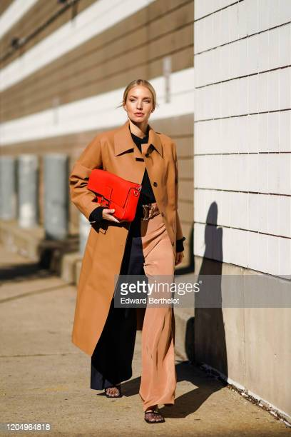 Leonie Hanne wears a red Fendi bag, a brown long coat, flared pants, outside Self Portrait, during New York Fashion Week Fall-Winter 2020, on...