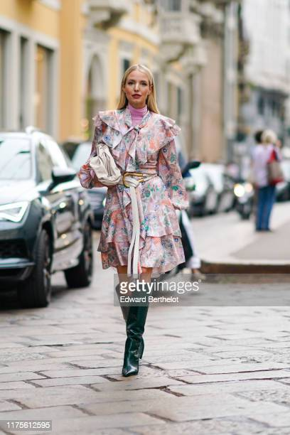Leonie Hanne wears a ruffled pink floral print dress, a pink turtleneck top, a white bag, green high leather boots, outside the Peter Pilotto show...