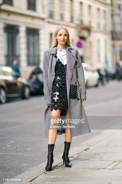 Leonie Hanne wears a trench coat with black and white houndstooth pattern print a glittering silver sequined dress with large black mesh and floral...