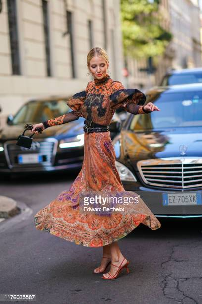Leonie Hanne wears a wears an orange and blue pleated dress with geormetric printed patterns and ruffles black leather belts a Jacquemus black mini...