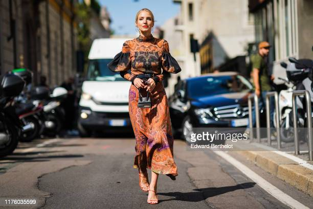 Leonie Hanne wears a wears an orange and blue pleated dress with geormetric printed patterns and ruffles, black leather belts, a Jacquemus black mini...