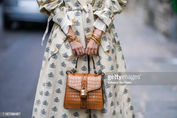 Leonie Hanne wears a white trench coat, and a brown crocodile pattern Chloe bag with a padlock, golden bracelet, in the streets of Paris, on October...