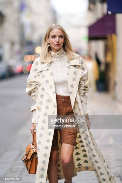 Leonie Hanne wears a white trench coat with printed monograms logos a Chloe brown leather crocodile pattern bag with a padlock brown houndstooth...