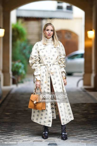 Leonie Hanne wears a white trench coat with printed monograms logos, a Chloe brown leather crocodile pattern bag with a padlock, golden bracelet,...