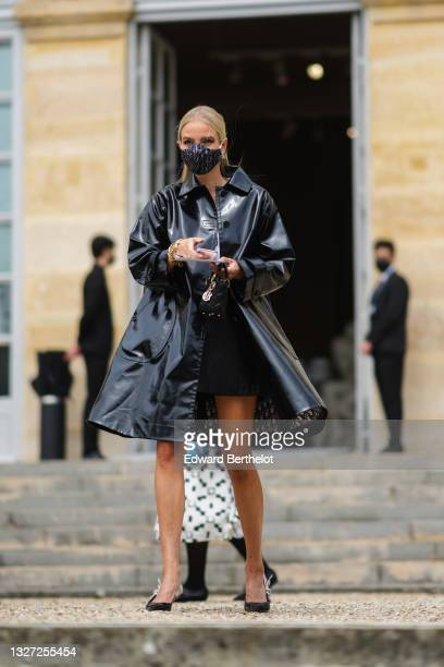 Leonie Hanne wears a white t-shirt with 'Revolution' slogan, black / pearls / rhinestones earrings from Christian Dior, a black shiny leather...