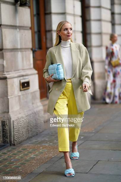 Leonie Hanne wears a white wool turtleneck pullover a pale green oversized blazer jacket a blue quilted Bottega Veneta bag yellow cropped pants blue...