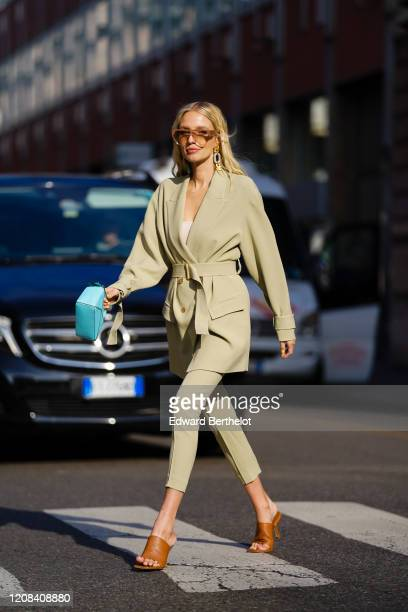 Leonie Hanne wears an oversized blazer beige jacket, a blue bag, cropped pants, brown sandals, outside BOSS, during Milan Fashion Week Fall/Winter...