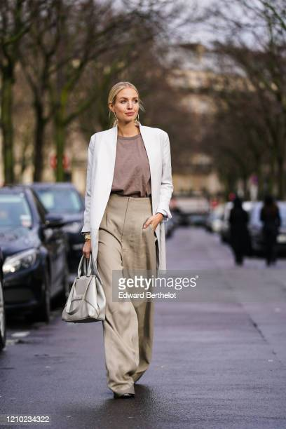 Leonie Hanne wears earrings, a bangle watch, a light brown top, a white jacket, a cream-color bag, sand-color wide-legs full-length pants, glittering...