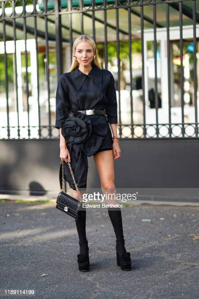 Leonie Hanne wears earrings, a black dress with an attached large flower, a belt, a black leather Miu Miu bag, long socks, black shoes, outside Miu...