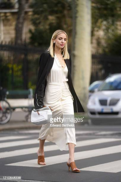 Leonie Hanne wears earrings, a black oversized jacket, a white dress, a white bag, brown pointy shoes, outside Gauchere, during Paris Fashion Week -...
