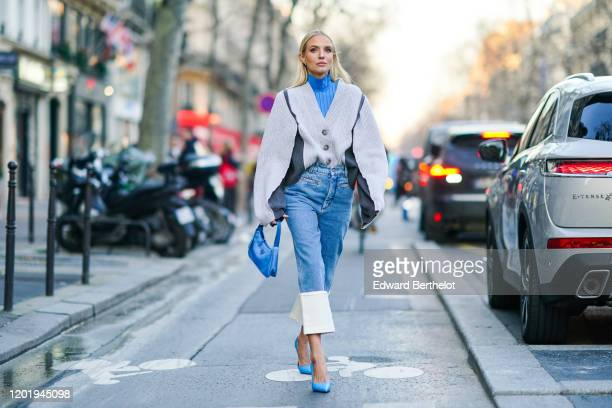 Leonie Hanne wears earrings, a blue turtleneck, a white oversized V-neck knit jacket with grey inserts, a blue Prada handbag, blue crop jeans with...