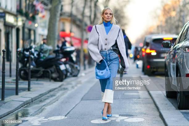 Leonie Hanne wears earrings, a blue turtleneck, a white oversized V-neck knit jacket with grey inserts, a blue Prada handbag, blue crop jeans with...