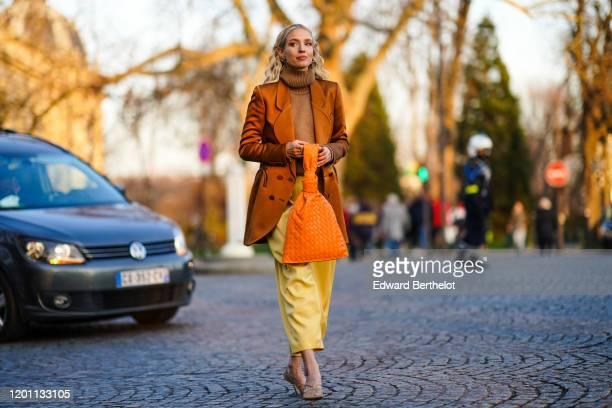 Leonie Hanne wears earrings, a brown knit turtleneck, a lustrous rust-color jacket, an orange woven leather bag, yellow leather crop pants, fishnet...