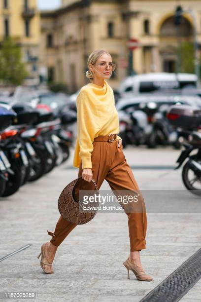 Leonie Hanne wears earrings, a fluffy yellow sweater with a scarf, rust-color pants, beige fishnet heeled pumps, a brown python pattern round...