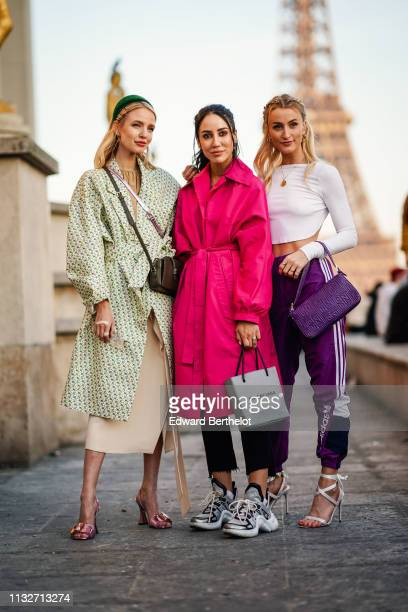 Leonie Hanne wears earrings a green hairband hairpins a camel gathered top a green floral print trench coat a brown handbag a beige skirt shiny...