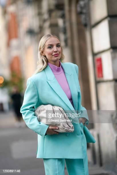 Leonie Hanne wears earrings a mauve hineck top a seagreen jacket matched pants a creamcolor quilted clutch outside Ralph Russo during Paris Fashion...