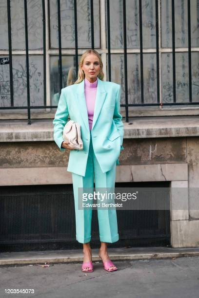Leonie Hanne wears earrings, a mauve hi-neck top, a sea-green jacket, matched crop cuffed pants, hot pink sandals, a cream-color quilted clutch,...