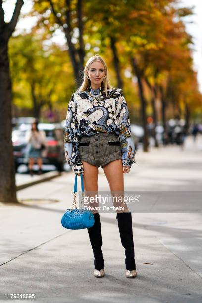Leonie Hanne wears earrings, a multicolor top with printed animals, a golden necklace, checkered pattern shorts, a blue quilted Miu Miu bag, black...