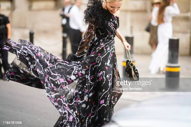 Leonie Hanne wears earrings, a necklace, a one- shoulder muslin flowing long dress with black feathers on one shoulder and cuff, a black sequined...