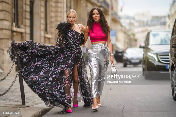 Leonie Hanne wears earrings, a necklace, a one- shoulder muslin flowing long front-slit dress with black feathers on one shoulder and cuffs, a black...