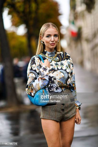 Leonie Hanne wears earrings, a necklace, a white long sleeves hi-neck blouse with grey swan and mermaids print, brown Prince of Wales shorts, outside...