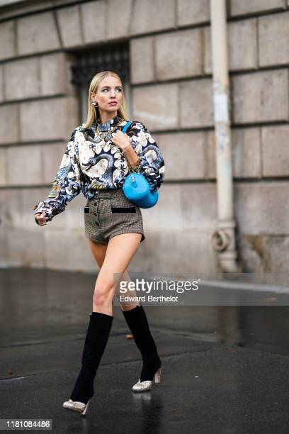 Leonie Hanne wears earrings, a necklace, a white long sleeves hi-neck blouse with grey swan and mermaids print, brown Prince of Wales shorts, a blue...