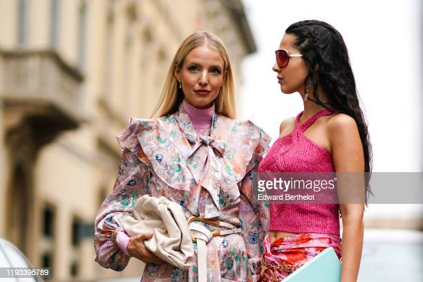 Leonie Hanne wears earrings, a pink turtleneck, a long sleeves, ruffled, light pink dress with colorful flowers print and a lavaliere, a white belt...