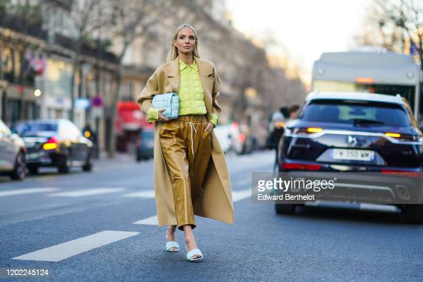 Leonie Hanne wears earrings, a pistachio-green quilted shirt, a beige coat, a Bottega Veneta light blue quilted clutch, light brown leather wide-legs...