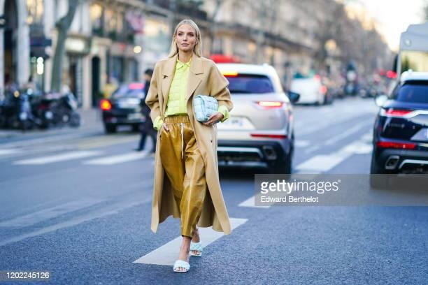 Leonie Hanne wears earrings, a pistachio-green quilted shirt, a beige coat, a Bottega Veneta light blue quilted clutch, light brown leather wide-legs...