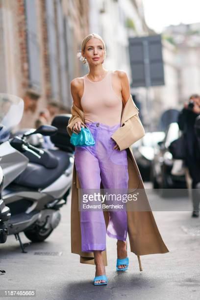 Leonie Hanne wears earrings a skintone sleeveless top a beige coat seethrough mauve widelegs crop pants blue heeled sandals a shiny blue puffy bag...