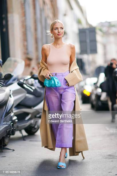 Leonie Hanne wears earrings a skintone sleeveless top a beige coat seethrough mauve widelegs crop pants blue heeled sandals a shiny blue puffy bag...