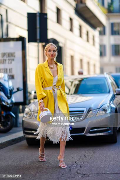 Leonie Hanne wears earrings, rings, bracelets, sunglasses, a chain necklace, a white dress with a wide neckline and decorated with white feathers, a...