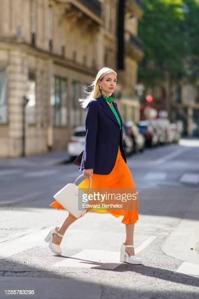 Leonie Hanne wears golden earrings, a golden necklace, a dark navy blue Prada blazer jacket, a green ruffled silky Prada shirt with frilly collar, a...