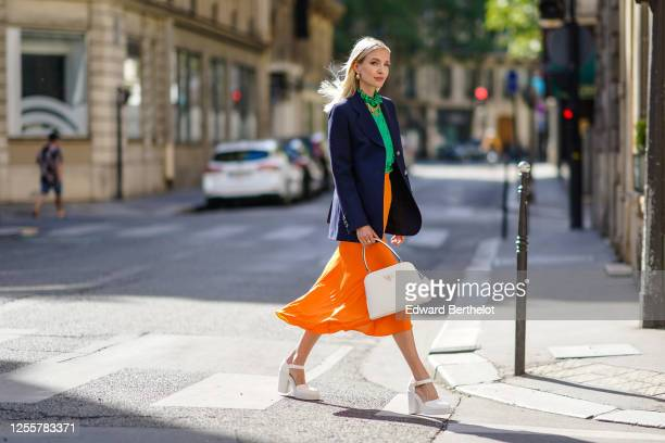 Leonie Hanne wears golden earrings a golden necklace a dark navy blue Prada blazer jacket a green ruffled silky Prada shirt with frilly collar a neon...