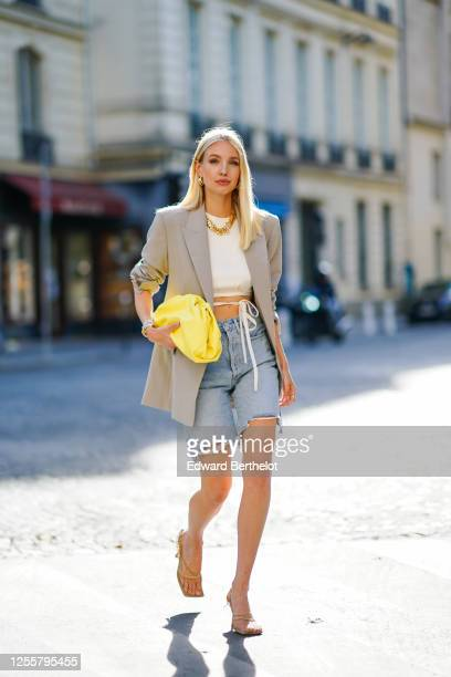 Leonie Hanne wears golden earrings, a golden necklace, a white cropped top from Orseund Iris, a gray oversized long blazer jacket from Frankie Shop,...