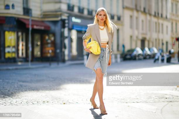 Leonie Hanne wears golden earrings a golden necklace a white cropped top from Orseund Iris a gray oversized long blazer jacket from Frankie Shop a...