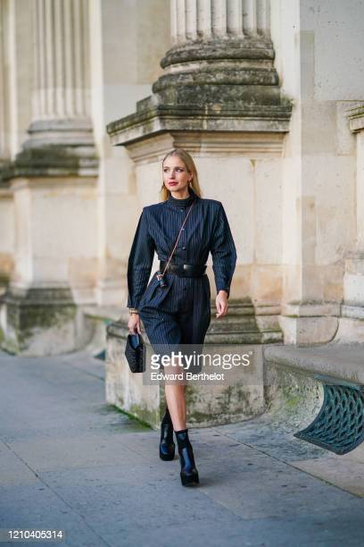 Leonie Hanne wears hair pins, a black long striped dress with shoulder pads, a black leather belt, a Vuitton cylinder shaped mini bag, a Vuitton bag,...