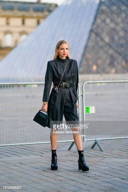 Leonie Hanne wears hair pins, a black long striped dress with shoulder pads, a black leather belt, a Vuitton cylinder shaped mini bag, a Vuitton bag,...