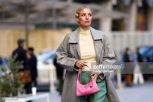 Leonie Hanne wears hair pins, a pale yellow pullover, a gray trench coat, green pants, a pink Prada fanny pack bag, during London Fashion Week...