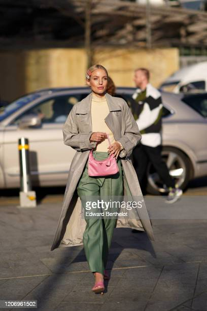 Leonie Hanne wears hair pins, a pale yellow pullover, a gray trench coat, green pants, a pink Prada fanny pack bag, pink shoes, during London Fashion...