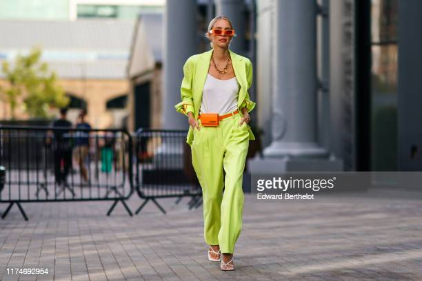 Leonie Hanne wears orange sunglasses from Gucci a neon green/yellow blazer jacket flare pants an orange belt bag from Jacquemus sandals a golden...