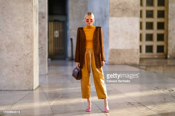 Leonie Hanne wears pink sunglasses, a brown long jacket with shoulder pads, an orange wool turtleneck pullover, cropped large pants, pink shoes,...