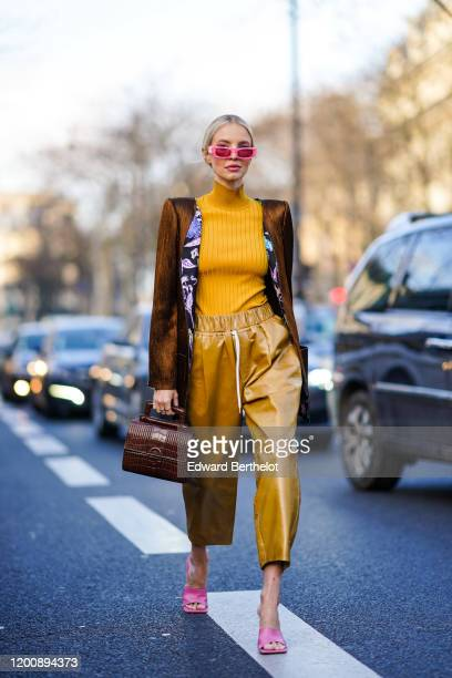 Leonie Hanne wears pink sunglasses, a brown long jacket with shoulder pads, an orange wool turtleneck pullover, cropped large pants, pink shoes, a...